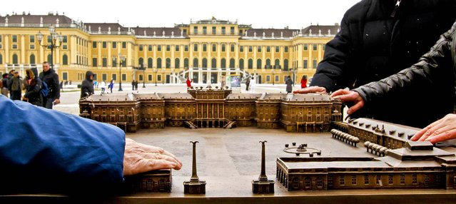 Two people touch a bronze replica of Schoenbrunn Palace during a presentation in front of the original palace in Vienna, Austria, on February 20, 2013. The 1:400 scale replica allows the visually impaired an opportunity to experience the castle through touch. (Photo by Ronald Zak/Associated Press)
