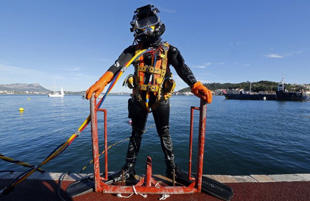 A commercial diver prepares to dive during a training session at the National Diving School in Saint-Mandrier near Toulon, South Eastern France, November 19, 2014. (Photo by Jean-Paul Pelissier/Reuters)