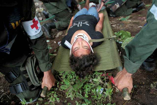 Nicaraguan army members carry a participant playing the role of a victim during a national multi-hazard drill organized by the National System for Prevention, Mitigation and Attention to Disasters (SINAPRED), in the 30 de Mayo neighborhood in Managua, Nicaragua, September 26, 2016. (Photo by Oswaldo Rivas/Reuters)