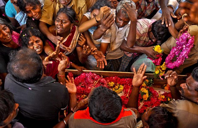 Family members of paramilitary soldier mourn by his coffin during his cremation ceremony in Peraiyur, India, on March 14, 2013. The man was among five soldiers that were killed during an attack by militants. (Photo by Associated Press)