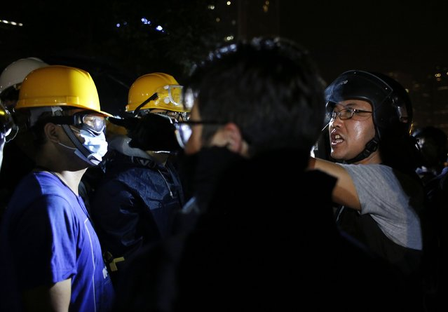 A riot policeman (R) shouts at pro-democracy protesters (L) during a confrontation outside government headquarters in Hong Kong early December 1, 2014. (Photo by Bobby Yip/Reuters)