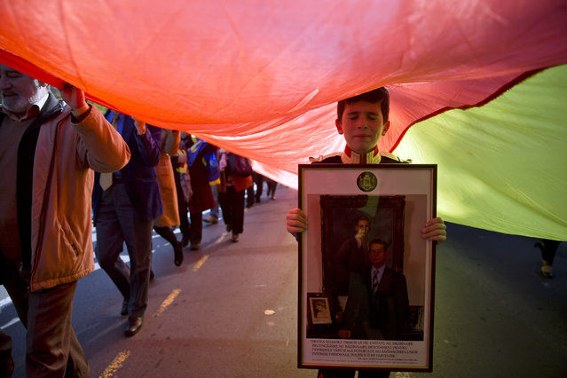 A Romanian boy, wearing a royal uniform holds a picture of former Romanian King Michael I as supporters of the monarchy march to celebrate the king's 94th birthday, in Bucharest, Romania, Sunday, October 25, 2015. Monarchy supporters carried a 150 meters long flag on a main boulevard in the Romanian capital to celebrate the former king's birthday. (Photo by Vadim Ghirda/AP Photo)