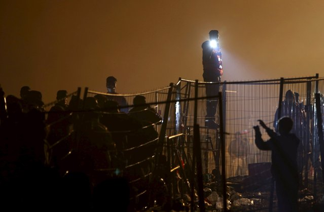 Austrian police guard migrants as they wait to cross the Slovenia-Austria border in Sentilj, Slovenia, October 27, 2015. (Photo by Srdjan Zivulovic/Reuters)