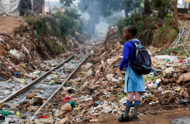 A schoolgirl stands next to the Kenya-Uganda railway line during the partial reopening of schools, after the government scrapped plans to cancel the academic year due to the coronavirus disease (COVID-19) pandemic, in Kibera slums of Nairobi, Kenya on October 12, 2020. (Photo by Thomas Mukoya/Reuters)