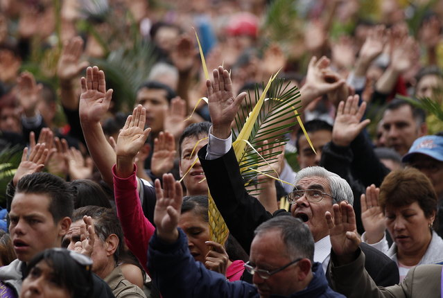 Faithful pray during a Palm Sunday Mass at the Baby Jesus Church in Bogota, Colombia, Sunday March 24, 2013. According to the New Testament, Palm Sunday marks the day Jesus rode into Jerusalem, greeted by cheering crowds bearing palm fronds. For Christians, Palm Sunday marks the start of Holy Week. The week continues with commemorations of Jesus' crucifixion on Good Friday before celebrating his resurrection on Easter the following Sunday. (Photo by Fernando Vergara/AP Photo)