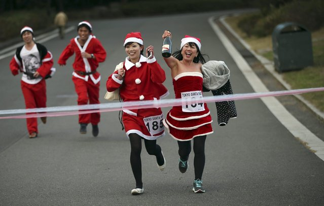 Participants in Santa Claus costume approach to finish during Santa Run at Kasai Rinkai Park in Tokyo, Saturday, December 6, 2014. Over 400 people participated in the 2.5 kilometer-run (1.5 miles). (Photo by Eugene Hoshiko/AP Photo)