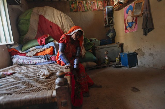 Seeta, a cotton picker, rocks her baby in a hammock in her room decorated with posters of Bollywood film stars in Meeran Pur village, north of Karachi November 23, 2014. (Photo by Akhtar Soomro/Reuters)