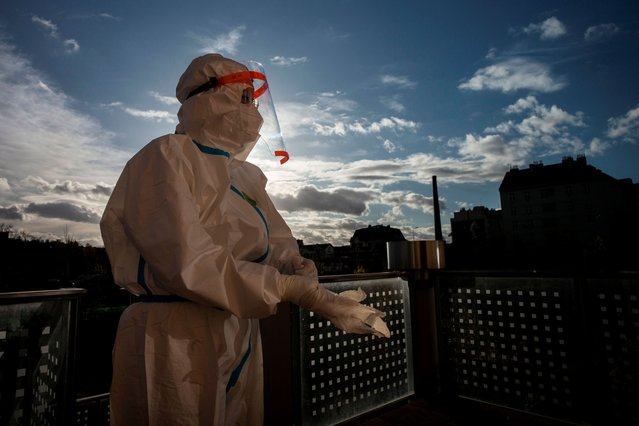 A medical worker wearing protective equipment puts on her gloves on the balcony of the nursing house on November 16, 2020 in Prague. The Czech Republic confirmed 1,887 COVID-19 cases on Sunday, which is the lowest daily rise since October 5, according to the latest data that the Health Ministry released on its website today. (Photo by Michal Cizek/AFP Photo)