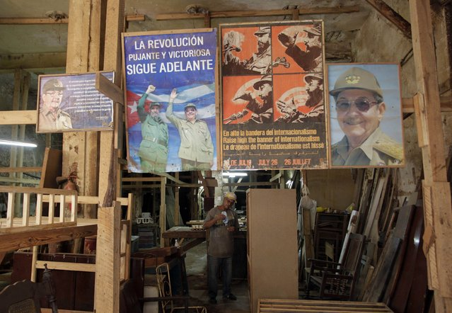 "Signs with photographs of Cuban President Raul Castro and his brother Fidel Castro hang outside a carpentry shop in Havana December 17, 2014. One of the signs (2nd L) reads, ""The powerful and victorious revolution"". (Photo by Reuters/Stringer)"