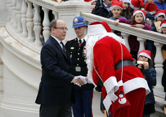 A man dressed as a Santa Claus greets Prince Albert II of Monaco (L) as he arrives to attend the traditional Christmas tree ceremony at the Monaco Palace as part of Christmas holiday season in Monaco, December 17, 2014. (Photo by Eric Gaillard/Reuters)