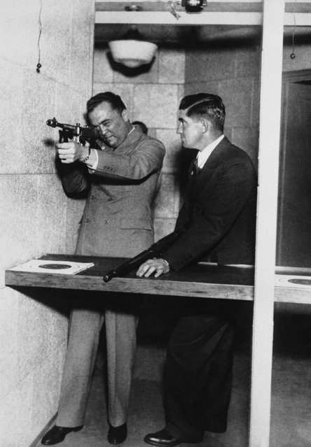 J. Edgar Hoover head of the FBI, demonstrates the use of a machine gun at the department of justice to Mickey Cochrane (right) manager of the Detroit tigers, in Washington, September 2, 1935, but Mickey needs little instruction as he is a well known Marksman and makes a hunting tour at the close of every baseball season. (Photo by AP Photo)