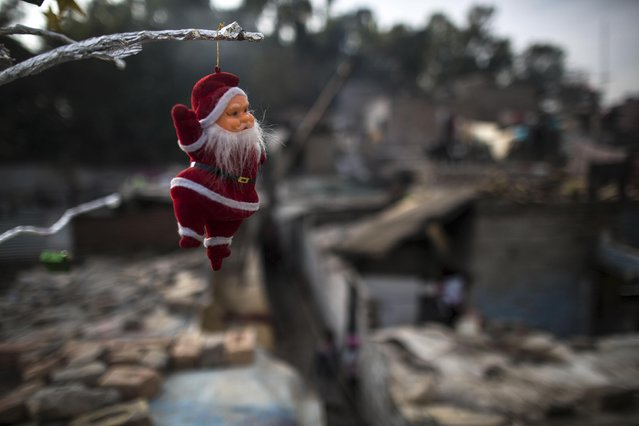 A Santa Claus figurine hangs from a tree ahead of Christmas in a Christian slum in Islamabad December 24, 2014. (Photo by Zohra Bensemra/Reuters)
