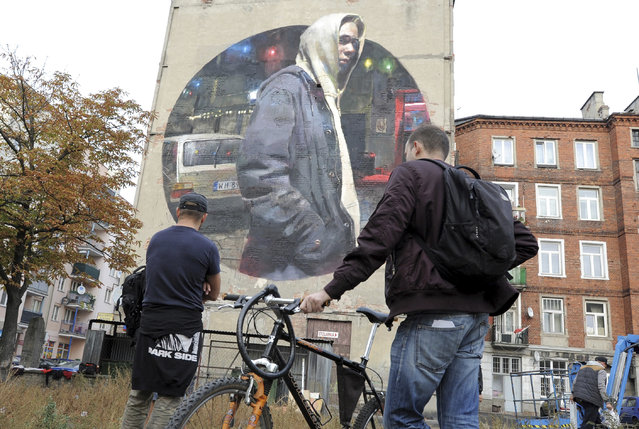 People look at a new mural by Spanish painter Sebas Velasco, created on a blank wall of an old house in the district of Praga, in Warsaw, Poland, Saturday, October 1, 2016. (Photo by Alik Keplicz/AP Photo)
