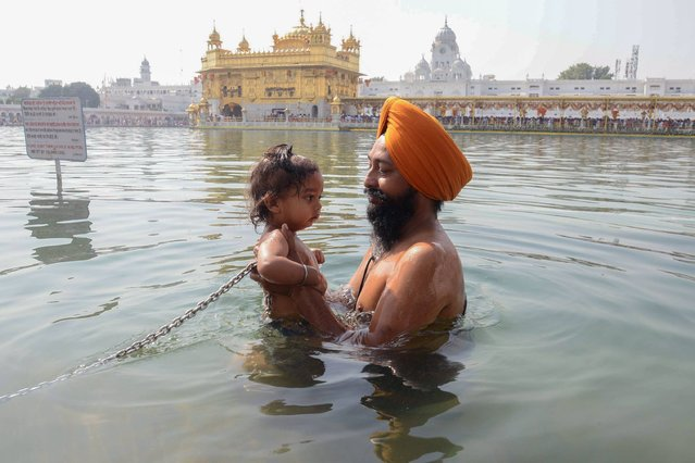 An Indian Sikh devotee bathes with his child in the holy sarovar (water tank) at the Sikh Golden Temple shrine in Amritsar on October 17, 2016. (Photo by Narinder Nanu/AFP Photo)