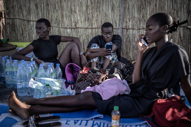 Models sit backstage during an outdoor show at Dakar Fashion week on December 12, 2020 just outside Dakar, Senegal. With Senegal's low incidence of Covid-19, Dakar's marquee fashion event looked markedly more normal than its counterparts in other global capitals, whose fashion weeks were heavily curtailed or canceled. (Photo by Finbarr O'Reilly/Getty Images)