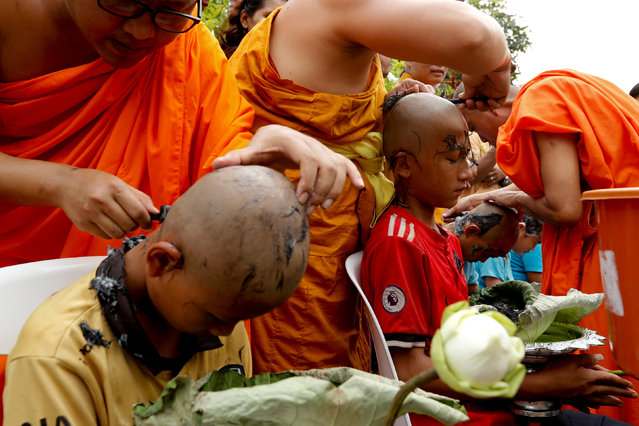 Boys have their hair shaved by monks in preparation for an annual Poy Sang Long celebration, a traditional rite of passage for boys to be initiated as Buddhist novices, in Mae Hong Son, Thailand, April 2, 2018. (Photo by Jorge Silva/Reuters)