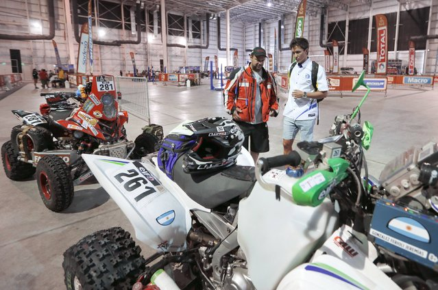 Argentine Yamaha's quad riders Alejandro Carlos Verza (L) and Jeremias Ferioli Gonzalez talk with while waiting for technical verification ahead of the Dakar Rally 2015 in Buenos Aires January 1, 2015. (Photo by Enrique Marcarian/Reuters)