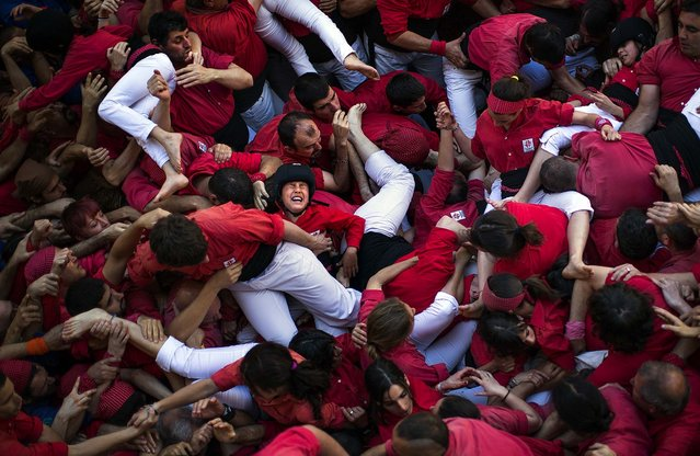 "Members of the Castellers of Barcelona crowd together after the collapse of their  ""castell"". A few participants were slightly wounded after the collapse of the human tower and were taken to a hospital. (Photo by Emilio Morenatti/Associated Press)"