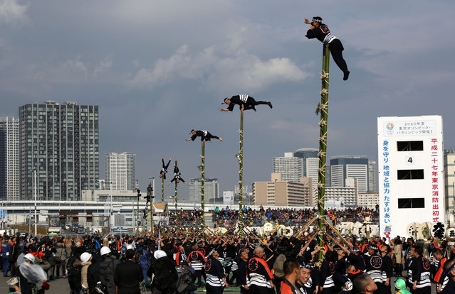 Members of a traditional firefighting preservation group perform ladder stunts during the annual New Year's Fire Brigade Review in Tokyo, Tuesday, January 6, 2015. (Photo by Eugene Hoshiko/AP Photo)