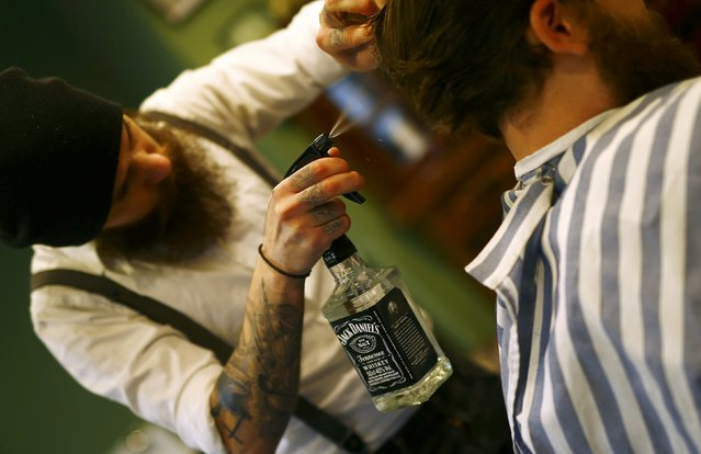"Alex ""Torreto"" Vellios, a 26-year old Greek-born barber uses a water filled Whiskey bottle to wet the hair of a customer at his Torreto barber shop in Frankfurt January 6, 2015. (Photo by Kai Pfaffenbach/Reuters)"