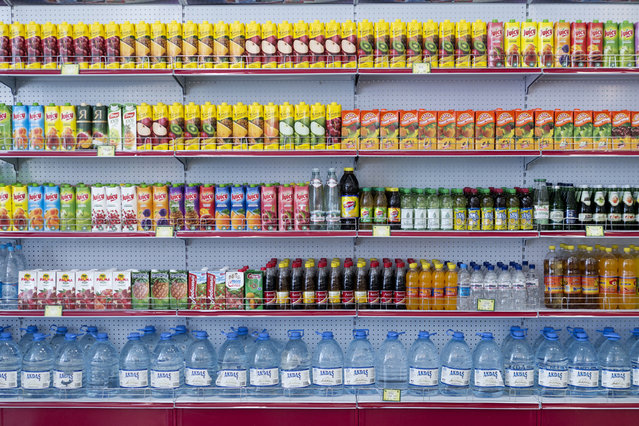 """Precisely stacked drinks in a store in the center of Ashgabat. The main street of the capital features lavish shops which were part of the architectural grand plan but are seldom used by locals. Daily life under the new president is reportedly easier than before when food shortages were common. """"We might not always be able to afford it, but the food is there"""" said one student. (Photo by Amos Chapple via The Atlantic)"""