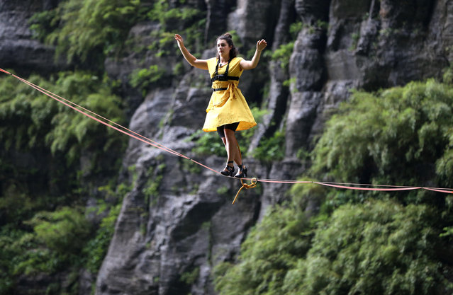 "Canadian slackliner Mia Noblet walks on a slackline (25mm wide, 3mm thick and 60m long) during ""Tianmen Mountain Female High-Heeled Highline Challenge"" at Zhangjiajie National Forest Park on May 27, 2018 in Zhangjiajie, Hunan Province of China. 23-year-old Canadian slackliner Mia Noblet became the first one who finished the challenge in 22 minutes and 36 seconds while 32-year-old French slackliner Mini Guesdon broke the record in 9 minutes and 24 seconds during her second attempt on Sunday. (Photo by VCG/VCG via Getty Images)"