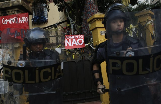 """Riot police stand in front of a sign that reads, """"No to fare hikes"""" hung on the gate of a house during a protest against fare hikes for city buses, subways and trains in Sao Paulo January 16, 2015. (Photo by Nacho Doce/Reuters)"""
