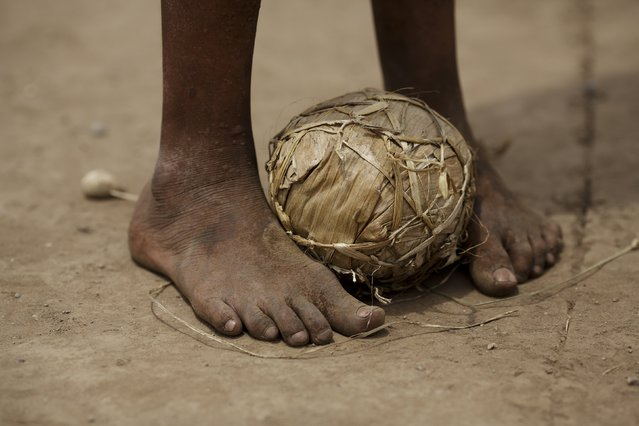 In this November 21, 2015 photo, a student stands barefoot with a ball constructed entirely of banana leaves, during Intercultural Educational Day events in Peru's Junin region. Hunger haunts the jungle home of the Ashaninka and the problem may be worst among children. (Photo by Rodrigo Abd/AP Photo)