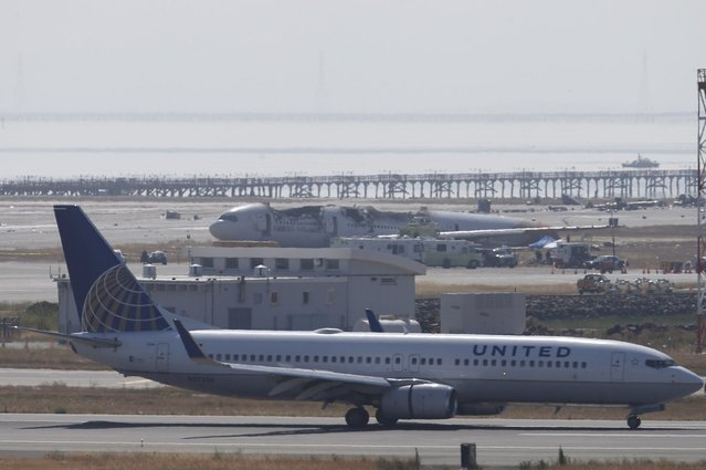 An United Airlines airliner taxis past the wreckage of Asiana Airlines flight 214 at San Francisco International Airport July 7, 2013. Air travel continues to be impacted the day after the Asiana's Boeing 777 from Seoul with 307 people on board crashed and burst into flames, killing two people and sending more than 180 to local hospitals. (Photo by Stephen Lam/Reuters)