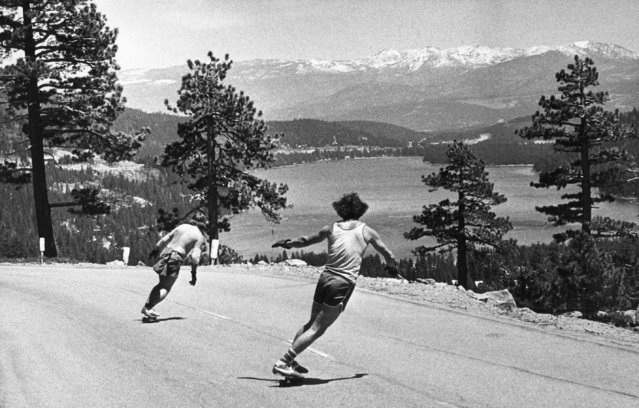 Dale Dox, left, of Squaw Vally, Calif., and Dennis Dunn of Truckee, Calif., go their way down old U.S. 40 alongside Donner Lake in California's high Sierras, on May 31, 1977. They were a part of a group of half a dozen people skateboarding at the 6,800-foot elevation and traveling some three miles on their downhill run over the weekend. (Photo by AP Photo)