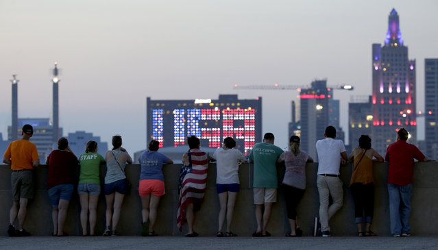 People wait for an Independence Day fireworks display, from a vantage point at the Liberty Memorial on Wednesday, July 4, 2018, in Kansas City, Mo. (Photo by Charlie Riedel/AP Photo)