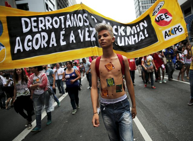 """A demonstrator wears stickers on his body with the image of Brazil's Lower House Speaker Eduardo Cunha reading """"Out Cunha, Coup"""" looks on during a protest against the impeachment proceedings against Brazil's President Dilma Rousseff, in Sao Paulo, Brazil, December 16, 2015. The banner reads, """"We have defeated Sao Paulo's State Governor Geraldo Alckmin, now is Cunha"""". (Photo by Nacho Doce/Reuters)"""