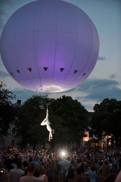 The Dream Engine Heliosphere, an enormous light-filled helium balloon that rises and falls and glides through the sky above the streets of Galwa suspending a stunning balletic aerialist who tumbles and turns from ground level to 20-metres above the audience, on July 24, 2013. (Photo by Andrew Downes)
