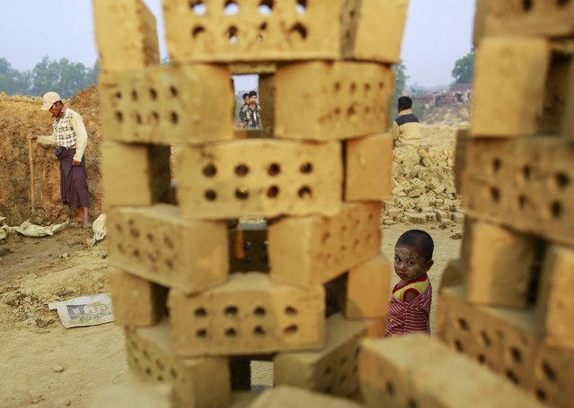 A girl stands while workers move bricks at a brick kiln on the outskirts of Yangon February 1, 2015. (Photo by Soe Zeya Tun/Reuters)