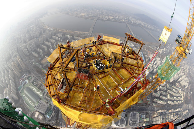 South Korean workers are seen from a crane as they work on the 123rd floor during the framing completion ceremony of the 'Lotte World Tower' in Seoul, South Kora, 22 December 2015. The building's exterior was completed in a final height of 550 meters, and 123 floors. The ceremony came five years and two months after the construction of the building began and its opening will likely take place at the end of next year when the interior work is set to be completed, the South Korean Yonhap news agency reported. (Photo by Jeon Heon-Kyun/EPA)