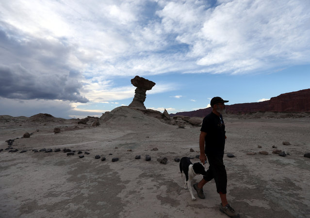 "A  man walks his dog near the rock formation called ""The Mushroom"" in the Valle de la Luna (Moon Valley) in the Ischigualasto Provincial Park, in San Juan, Argentina November 13, 2016. (Photo by Enrique Marcarian/Reuters)"
