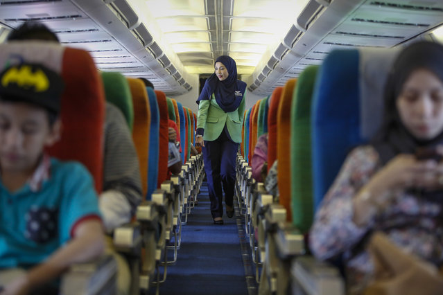 In this December 22, 2015, photo, a Rayani Air flight crew walks down the aisle on board before departure at Kuala Lumpur International Airport 2 in Sepang, Malaysia. (Photo by Joshua Paul/AP Photo)