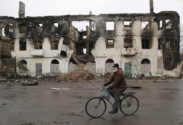 A resident rides his bicycle past a destroyed building in the town of Vuhlehirsk, Ukraine, Friday, February 6, 2015. (Photo by Petr David Josek/AP Photo)