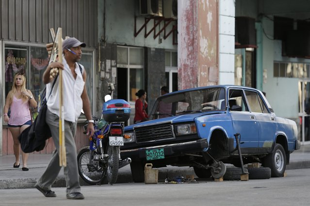 People walk past a Lada that is being repaired on a street in Havana February 7, 2015. The former Soviet Union began exporting its cheaply built models to Cuba in the 1970s until production began to peter out a decade ago. Very little evidence of Soviet influence remains in Cuba, except the spunky little Russian-made Lada cars, famous for rattling chassis but sturdy engines. (Photo by Enrique De La Osa/Reuters)