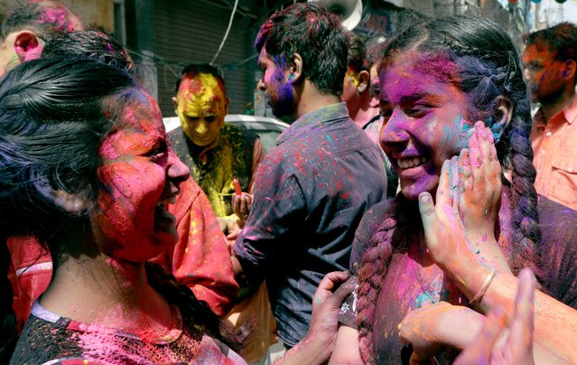 Indian people apply color on each other during Holi festival celebrations in Jammu, the winter capital of Kashmir, India, 28 March 2021. (Photo by Jaipal Singh/EPA/EFE)