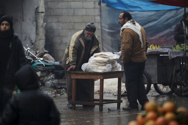 A street vendor sells bread during cold weather in the rebel-controlled area of Maaret al-Numan town in Idlib province, Syria January 4, 2016. (Photo by Khalil Ashawi/Reuters)
