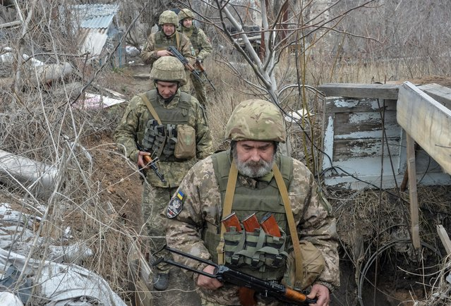 Service members of the Ukrainian armed forces walk at fighting positions on the line of separation from pro-Russian rebels near Donetsk, Ukraine on April 11, 2021. (Photo by Oleksandr Klymenko/Reuters)