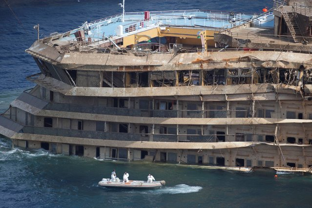 Workers on a boat sail past the Costa Concordia ship after it was lifted upright, on the Tuscan Island of Giglio, Italy, Tuesday, September 17, 2013. Engineers declared success on Tuesday as the Costa Concordia cruise ship was pulled completely upright during a complicated, 19-hour operation to wrench it from its side where it capsized last year off Tuscany, an unprecedented feat that sets the stage for it to be towed away next year. (Photo by Andrew Medichini/AP Photo)