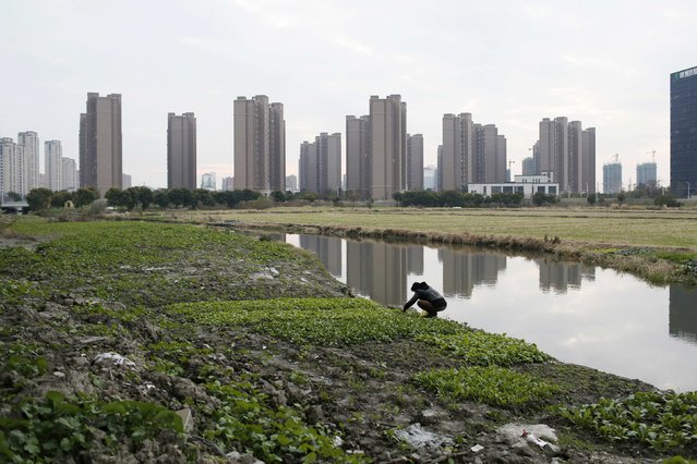 A farmer works on a wasteland near a construction site of new residential buildings in a suburb in Shanghai in this December 9, 2014 file photo. As China pulls out the stops to get more lending into its economy to bolster flagging growth, farming, a sector that employs almost a third of its 1.4 billion people, remains in desperate need of funding. (Photo by Aly Song/Reuters)