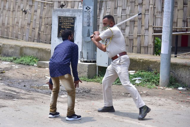 A police officer wields his baton against a man as a punishment for defied curfew due to rise of COVID-19 coronavirus cases in Nagaon District of Assam, India on May 16, 2021. (Photo by Anuwar Hazarika/NurPhoto via Getty Images)