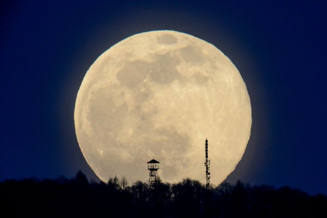 The full moon rises above the Karancs Hills pictured from Karancskeszi, Hungary, 28 March 2021. (Photo by Peter Komka/EPA/EFE)