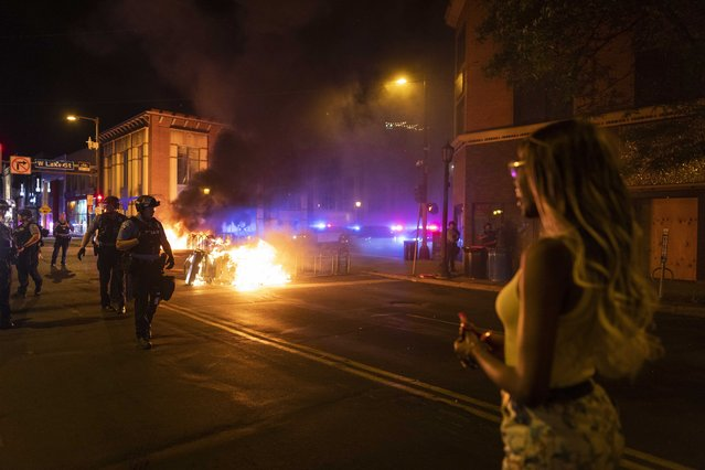 Police stand guard after protesters set fire to dumpsters on the street after a vigil was held for Winston Boogie Smith Jr. early on Saturday, June 5, 2021. Smith was shot and killed by law enforcement officers on Thursday during an arrest warrant operation. (Photo by Christian Monterrosa/AP Photo)