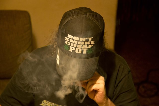 In this October 21, 2013 photo, Daniel, who did not want to give his last name, smokes marijuana he grew in a hydroponics garden inside his apartment in Mexico City. The market for gourmet weed is still minuscule next to the multibillion-dollar marijuana export trade dominated by the cartels. Like others, Daniel ordered seeds online from a company in Spain, opting for a U.K-originated strain known as Exodus Cheese. (Photo by Eduardo Verdugo/AP Photo)