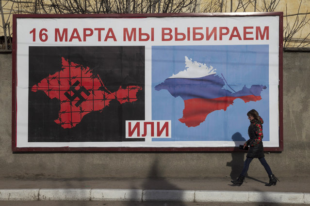 "A woman walks by a poster calling people to vote in the upcoming referendum, in Sevastopol March 10, 2014. The poster reads, ""On 16 March, we are choosing"" and ""or"" (bottom). (Photo by Baz Ratner/Reuters)"