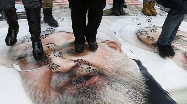 People walk over a portrait of Iran's President Hassan Rouhani as they take part in a protest against his visit to France in central Paris, France, January 28, 2016. (Photo by Jacky Naegelen/Reuters)